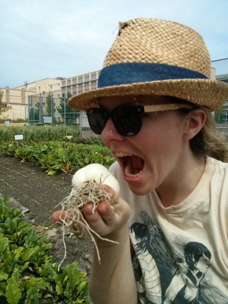 SOYL 2 leader, Shoshana, getting ready to take a bite of our first giant head of garlic!